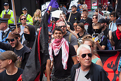 "London, June 21st 2014. A handful of masked ""anarchists"" join the thousands strong March Against Austerity in London."
