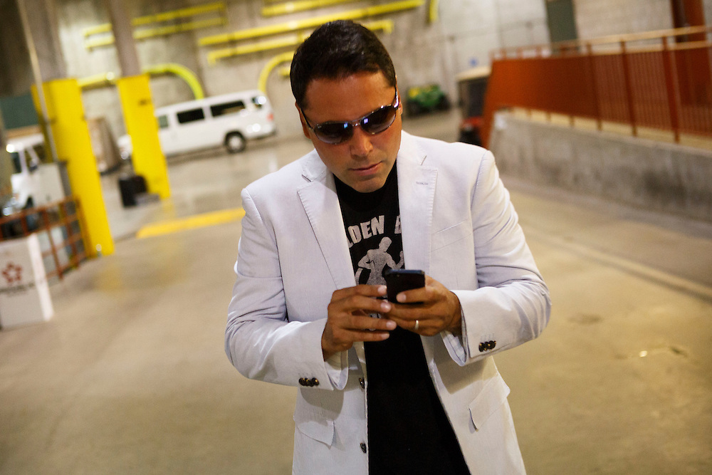 Oscar De La Hoya checks his iPhone as he arrives for the Victor Terrazas v Leo Santa Cruz WBC Super Bantamweight Title Fight, and Abner Mares v Jhonny Gonzalez, WBC Featherweight Title Fight, promoted by Golden Boy Productions at the StubHub Center on Saturday, August 24, 2013 in Carson, California. Patrick T. Fallon/For The New York Times