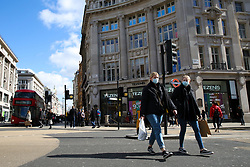 © Licensed to London News Pictures. 16/03/2020. London, UK. People wearing face masks on a nearly empty Oxford Street, just before 12 noon, amid an increased number of Coronavirus (COVID-19) cases in the UK. 35 coronavirus victims have died and 1,372 have tested positive for the virus in the UK as of 9am on Sunday, 15 March 2020. Photo credit: Dinendra Haria/LNP