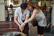 25 MARCH 2010 - BANGKOK, THAILAND: People rinse their hands in holy water after praying at the Erawan Shrine in Bangkok. The Erawan Shrine (Thai: San Phra Phrom) is a Hindu shrine in Bangkok, Thailand that houses a statue of Phra Phrom, the Thai representation of the Hindu creation god Brahma. The Erawan Shrine was built in 1956 as part of the government-owned Erawan Hotel to eliminate the bad karma believed caused by laying the foundations on the wrong date. The hotel's construction was delayed by a series of mishaps, including cost overruns, injuries to laborers, and the loss of a shipload of Italian marble intended for the building. Furthermore, the Ratchaprasong Intersection had once been used to put criminals on public display. An astrologer advised building the shrine to counter the negative influences. The Brahma statue was designed and built by the Department of Fine Arts and enshrined on 9 November 1956. The hotel's construction thereafter proceeded without further incident.      PHOTO BY JACK KURTZ