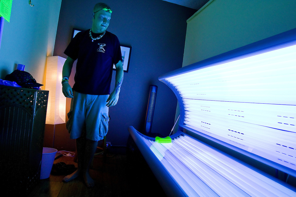 JEROME A. POLLOS/Press..Kellen Munden prepares for a tanning session Wednesday at Caribbean Tan in Coeur d'Alene. Beginning today, a 10 percent tax will be placed on tanning services under the new healthcare law.