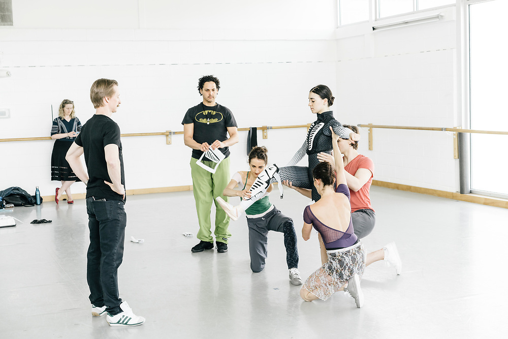 Dancers, including Nicole Graniero, left, Morgann Rose, right, and Tamas Krizsa, far right, along with ballet master Luis R Torres, center, place part of Sarah Steele's  specially designed space suit on during rehearsals for Frontier on May 3, 2017. The piece is Julie Kent's' first commission as new director'. The ballet is about space exploration, and the costumes, designed by Ted Southern of Final Frontier Design, look similar to what astronauts wear.