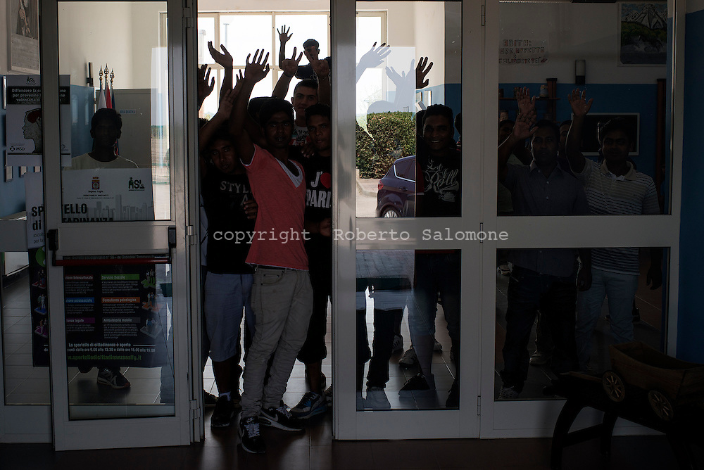 Cerignola, Italia - 22 agosto 2013. Immigrati ritratti all'interno di una struttura di accoglienza a Cerignola giocano a biliardino.<br /> Ph. Roberto Salomone Ag. Controluce<br /> ITALY - Immigrants are seen inside a welcome accomodation center for immigrants in Cerignola in  the italian southern region of Puglia on August 22, 2013.