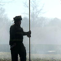 Guntown firefighter and EMT William Dallas stands in the smoke and mist holding a Pike Pole as he works as a Safety Officer during the Doggie Do's fire in Saltillo on Wednesday.