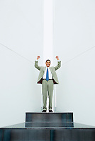 A smiling cheering / triumphant / exuberant mid 30's Asian business man standing atop a platform with arms raised overhead and clenched fists in a white room with a long vertical window behind him..20050916_MR_A.20050916_PR_A