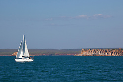 A small yacht sails past Hall Point in Camden Sound.