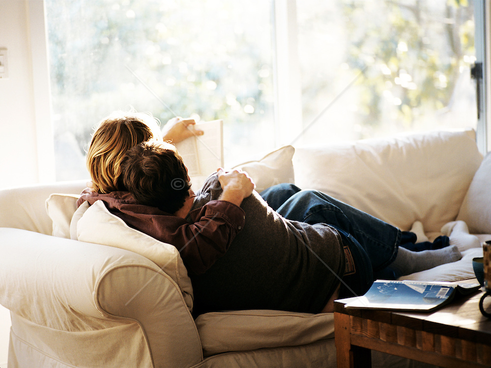gay couple reading a book together at home on the couch