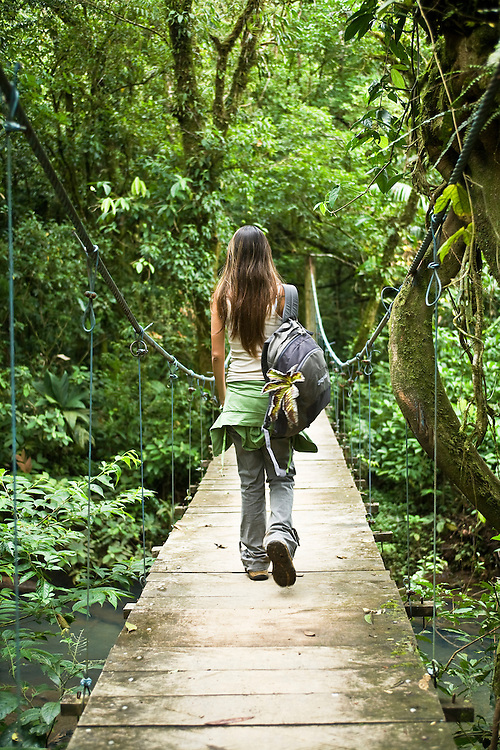 A woman walks away and across a suspension foot bridge in the forest at Tenorio National Park in Guanacaste, Costa Rica.