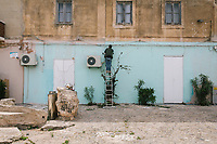 LAMPEDUSA, ITALY - 30 APRIL 2019: A worker paints a wall in via Roma, the main street of Lampedusa, Italy, on April 30th 2019.<br /> <br /> Since the early 2000s, the island has become a primary European entry point for migrants, mainly coming from Libya. In 2011, many more immigrants moved to Lampedusa during the rebellions in Tunisia and Libya. By May 2011, more than 35,000 immigrants had arrived on the island from Tunisia and Libya. By the end of August, 48,000 had arrived.
