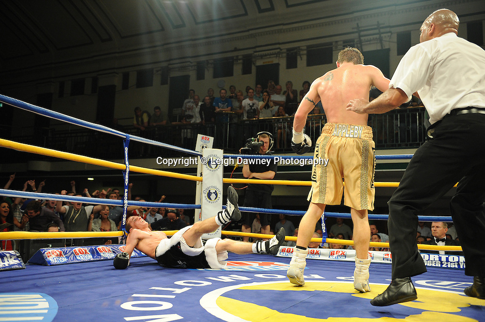 Liam Walsh (black/white shorts) is knocked down by Paul Appleby at The Commonwealth Super-Featherweight Championship at York Hall, Bethnal Green, London on Friday 30th September 2011. Box Nation.tv's debut live TV Channel 456 on Sky. Photo credit: © Leigh Dawney. Queensberry Promotions.