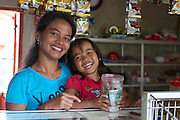 Jula Eha and her daughter counting the days takings in their small shop outside the front of their house in a quiet residential area near the town of Bogor, Indonesia.<br /> <br /> Her shop had mixed success at first and she used to become demotivated, but after subscribing to Usaha Wanita she regained her motivation and started to think of more creative ways to make her business a success. <br /> <br /> As a result her profits have increased and she is now saving money in an education fund for her children. <br /> <br /> She has also been able to follow Usaha Wanita's advice on savings and investments and she has joined a savings scheme and purchases new fridges and display cabinets for her store.