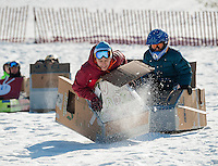 Adin Cisneros has a bumpy ride in his USA Sled during Gilford Parks and Recreations annual Cardboard Sled Derby at the Gilford Outing Club Wednesday morning.  Cisneros took home 1st in the Most Spectacular Wipeout Division.   (Karen Bobotas/for the Laconia Daily Sun)