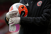 Football - 2019 / 2020 Premier League - Sheffield United vs Tottenham Hotspur<br /> A match ball is carried by an assistant carrying Disinfectant and wearing gloves, at Bramall Lane.<br /> <br /> COLORSPORT/PAUL GREENWOOD