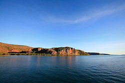 Mangroves line the shortline under red sandstone cliffs at the mouth of the Hunter River on the Kimberley coast.