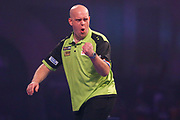 Michael van Gerwen wins a game and celebrates by punching the air during the 2019 William Hill World Darts Championship Final at Alexandra Palace, London, United Kingdom on 1 January 2019.