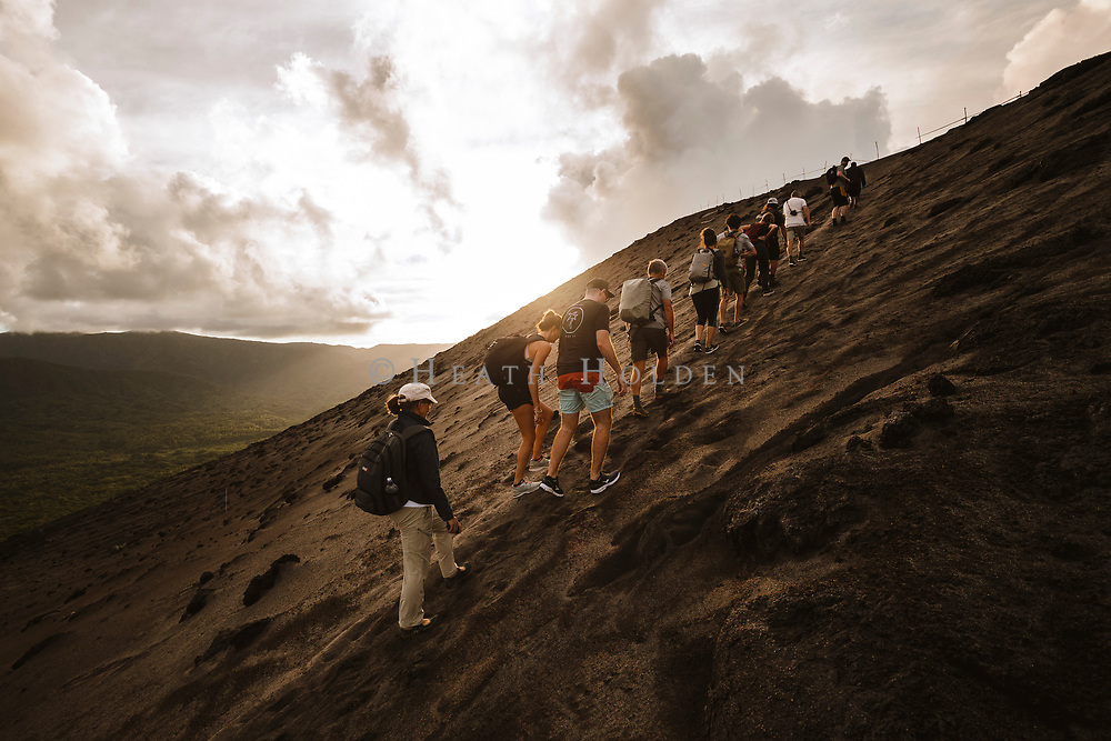 A groupd of travellers hike up the slopes of Yasur volcano during a tour around the volcano rim trail.
