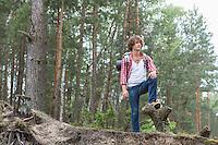 Full length of male backpacker standing in forest