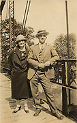 Couple standing on a bridge.