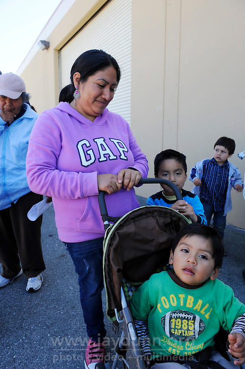 Families wait patiently in line to receive basics as well as occasional fresh vegetables at The Breadbox Center in east Salinas, a bimonthly distribution point supplied by the Food Bank of Monterey County.
