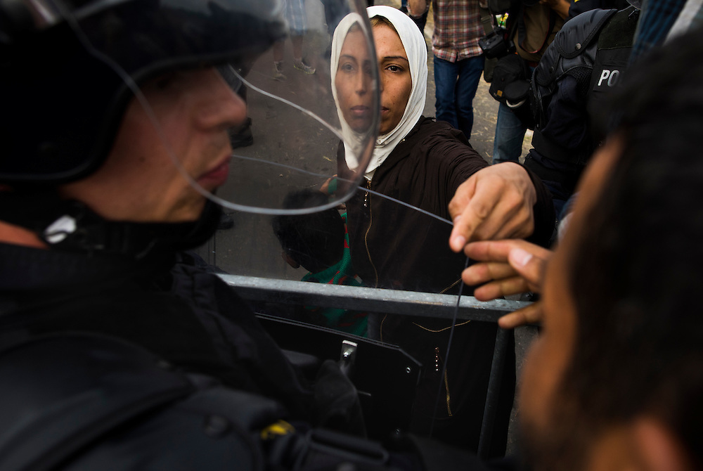 A woman asks a police officer to let her and her family through the Slovenian border on September 19, 2015 in Harmica, Croatia.