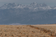 Snow capped Sangre de Cristo Mountains of Southern Colorado sit behind a fenceline near the Great Sand Dunes National Park and Preserve.