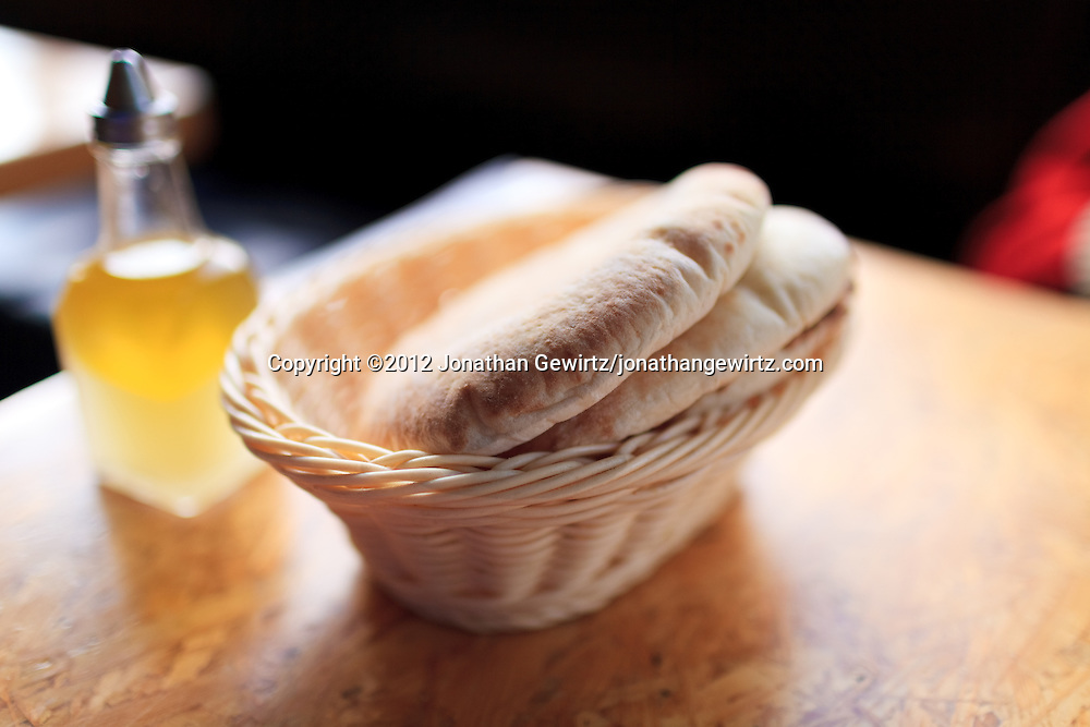 Loaves of warm pita bread in a wicker basket on a restaurant table. WATERMARKS WILL NOT APPEAR ON PRINTS OR LICENSED IMAGES.