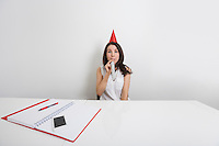Portrait of happy businesswoman in party hat blowing horn at desk in office