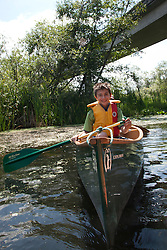 North America, United States, Washington, Bellevue, boy kayaking under highway bridge in Mercer Slough Nature Park.  MR