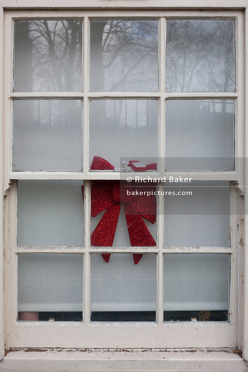 The remains of Christmas with a ribbon decoration in a sash window, on 11th January 2017, in London, England.