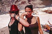 women crossing arms drinking in shade, Middle East Tek, Wadi Rum, Jordan, 2008
