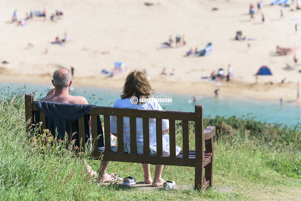 A couple of holidaymakers enjoy the sunny weather as they sit on a bench overlooking Crantock Beach in Newquay, Cornwall.