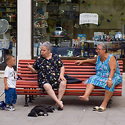 Grandmother sitting on red bench with friend talking to small boy, Venice, Italy<br />