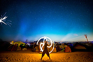 October 8, 2016 - Sunny Stone spins fire poi at his campsite, Dirt Camp during Joshua Tree Music Festival in Joshua Tree, California. Photo manipulation: fireworks added in post. (Photo by: Foster Snell)
