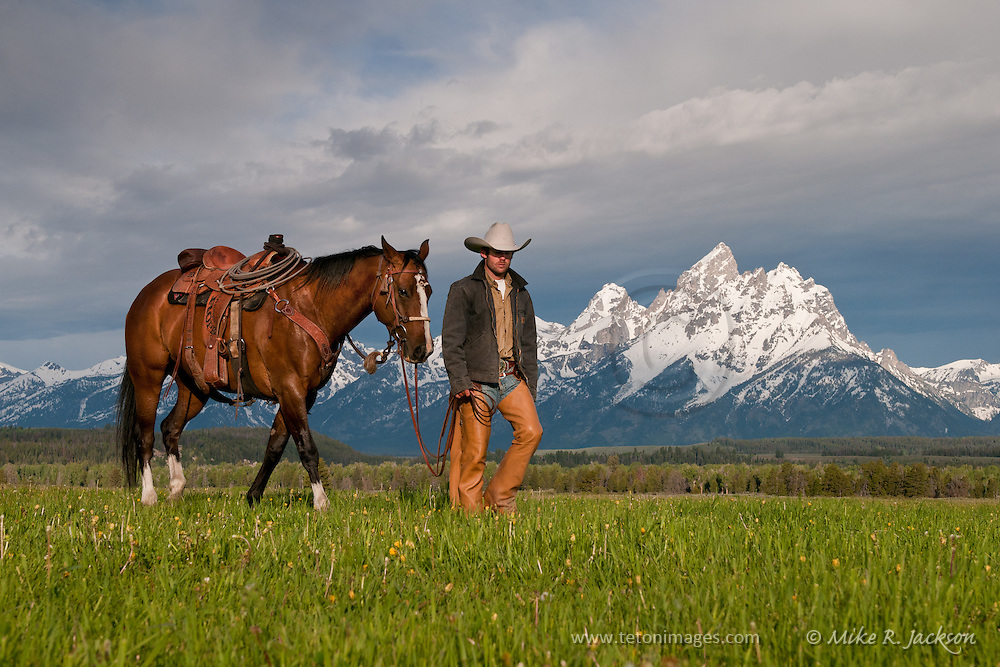 A wrangler and his horse walking in front of the Grand Teton mountain range in historic Jackson Hole, WY