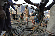 Workers uncoiling a thick steel-made cable (to tie ship parts and bring them closer to the beach with a winch).