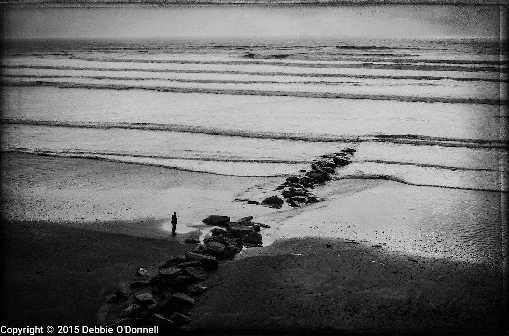 Small waves break on the shore as a man standing next to rocks extending into the water, watches the sun go down on Inch Beach, Dingle Peninsula.