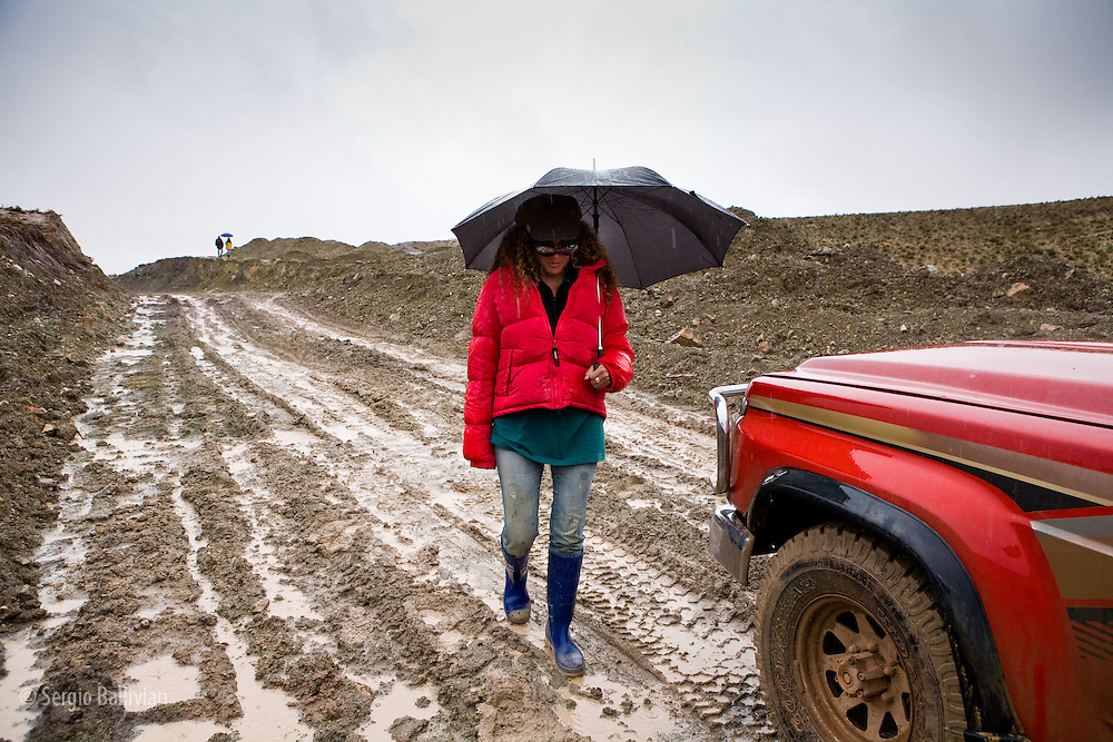 Adventure travelers wait for the rain to stop on the Altiplano during the summer rainy season as the roads are impassable due to high water.