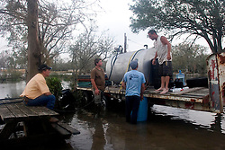 25 Sept, 2005. Carlyss, Louisiana. Hurricane Rita aftermath. <br /> Friends and relatives help neighbour Harold Herman (white t/rt) to syphon diesel fuel from a 500 gallon drum for use in his generator. Locals helped each other through the aftermath of the storm.<br /> Photo; &copy;Charlie Varley/varleypix.com