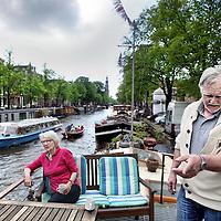 Nederland, Amsterdam , 18 mei 2012..Hij is een beschaafd mens en dus is het hem niet aan te zien, maar woonbootbewoner Hans Paalman (64, consultant in ruste) is 'wit-verzengend-heet'. Stadsdeel Centrum wil bij de Noordermarkt 'een open afstapplaats' voor rondvaartboten maken, waardoor zijn boot moet verkassen. En die van zijn buurman ook. Paalman staat naast zijn 23 meter lange schip uit 1906, dat in de Prinsengracht ligt. Zijn blik verraadt diepgewortelde trots op het schip, dat hij onlangs geheel heeft laten opknappen..Op de foto Hans Paalman en overbuurvrouw Mieke van Kasbergen..Foto:Jean-Pierre Jans