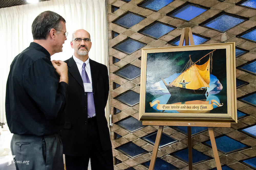 Artist Edward Riojas shows Rev. Kristian Bjornstadt (Eastern District DDRC) his painting of Jesus, whom even the winds obey. Bjornstadt serves as the District Disaster Response Coordinator for the LCMS Eastern District.