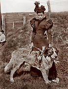 Well dressed woman with a Saint Bernard dog out in a country setting. circa 1900.