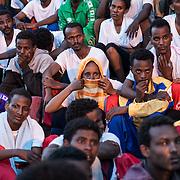 """donna eritrea di religione cristiana seduta in mezzo a ragazzi eritrei durante la manifestazione """"no finger print"""" davanti alla chiesa di Lapedusa."""