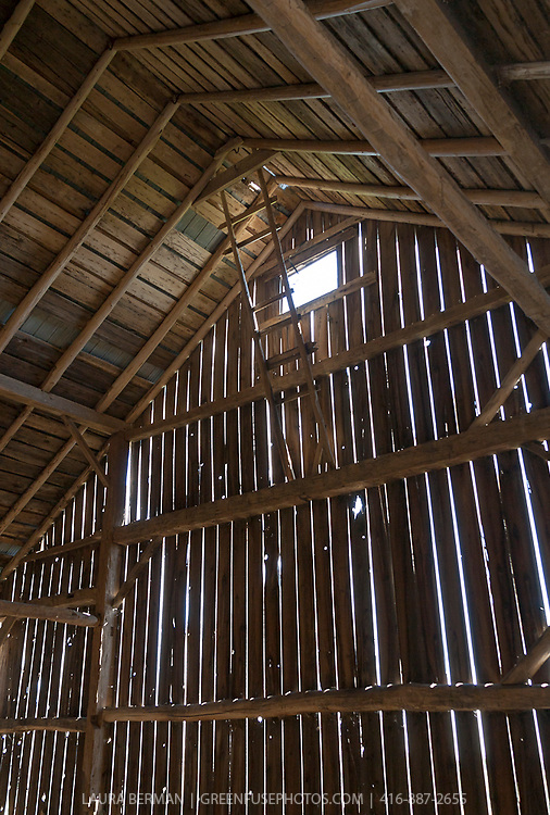 The hayloft of an old barn with wiude spacing between the boards for ventilation.