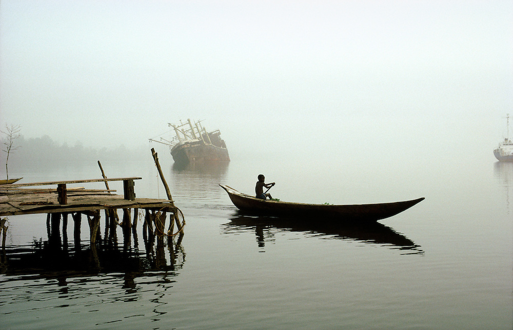 River Niger delta, Bendel State, Nigeria. Boy paddles canoe at Bennett Island Anchorage on the Warri River shipping channel.