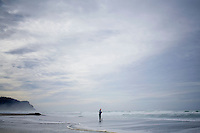 A fisherman stands in the ocean waves as he fishes in the early morning in Neskowin, Oregon