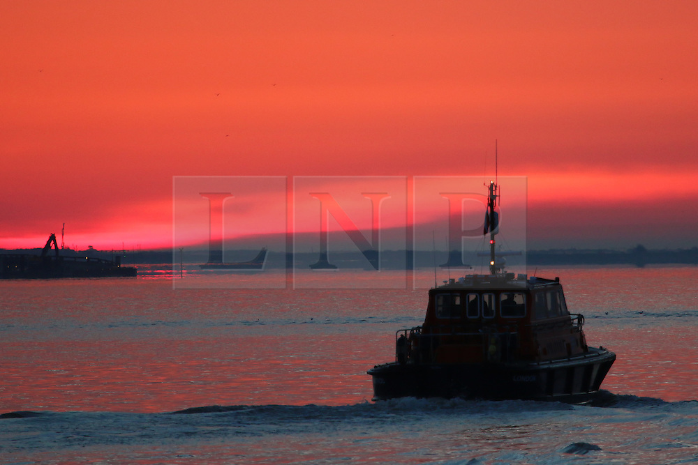 © Licensed to London News Pictures. 13/04/2016. Sunrise seen this morning over the Thames at Gravesend in Kent. A Port of London Authority boat returns to base. Credit : Rob Powell/LNP