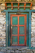 A red and blue-green door in Nepal.