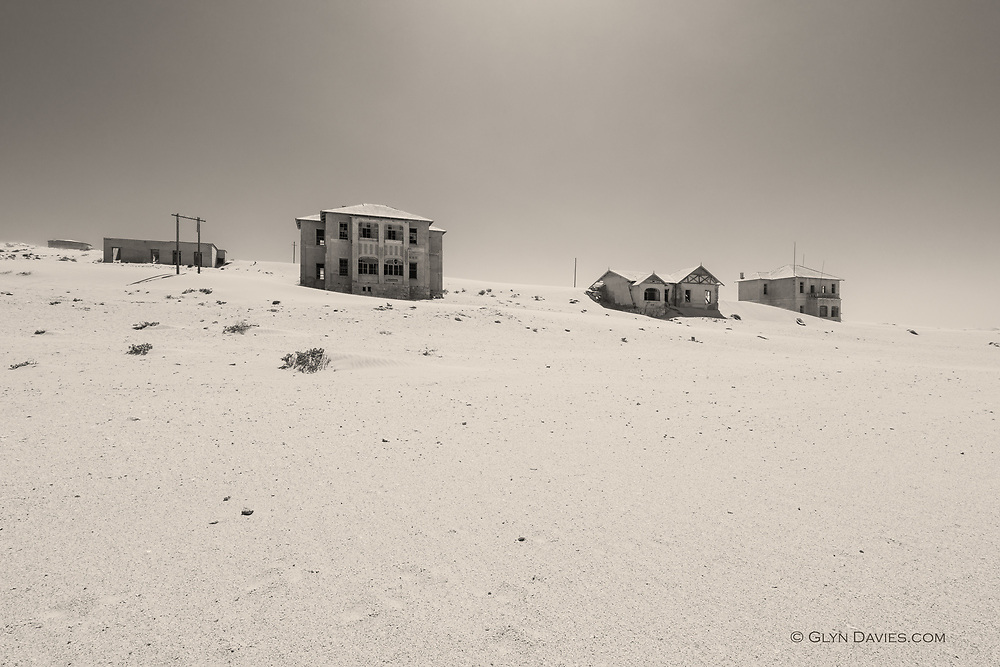 Nominated image in the 13th Black & White Spider Awards 2018<br /> <br /> <br /> This is the deserted mining town of Kolmonskop in Western Namibia. In 1909 diamonds were found here and this industrial hamlet developed. The nearby harbour town of Lüderitz nearby also gained rapid prosperity.<br /> <br /> Since then however diamonds are mostly found elsewhere and so these towns went into decline. This small industrial complex is forever fighting to remain above the gale-blown desert sands but this and Lüderitz are still incredible places to visit as so little has changed at all since the early twentieth century.<br /> <br /> It's quite eerie standing inside the large derelict buildings, the winds literally howling through the broken windows and doors and dunes almost visibly being created in front of your eyes.
