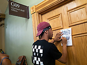19 JUNE 2020 - DES MOINES, IOWA: MATTHEW BRUCE, from Des Moines, leaves a note on the Governor's door during a Black Lives Matter Juneteenth rally in the Iowa State Capitol. About 100 supporters of Des Moines Black Lives Matter finished their week long series of protests at the Iowa State Capitol with a Juneteenth rally and demonstration. They are demanding that Gov. Kim Reynolds use an executive order to restore voting rights to felons who have completed their sentences. The protesters did not meet with the Governor Friday. The protest was peaceful. PHOTO BY JACK KURTZ