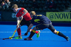 Holcombe's James Kitcherside is tackled by Sam Hartherley of Team Bath Buccaneers. Holcombe v Team Bath Buccaneers - Now: Pensions Finals Weekend, Lee Valley Hockey & Tennis Centre, London, UK on 12 April 2015. Photo: Simon Parker